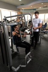 Woman Exercising Chest With Her Personal Trainer