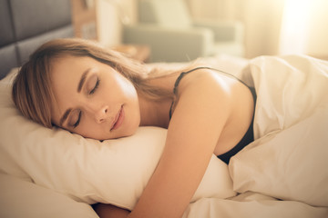 Young woman sleeping in bed. Morning time.