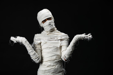 Studio shot portrait  of young man in costume  dressed as a halloween  cosplay of scary mummy pose like a open hand acting on isolated black background Fototapete