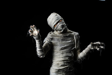 Studio shot portrait  of young man in costume  dressed as a halloween  cosplay of scary mummy pose like a clamber acting on isolated black background
