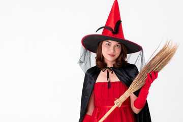 Woman in red dress costume for famale witch holding broomstick on white background with copy space. Concept for funny activity in halloween festival