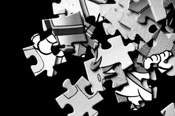 Pieces of children's puzzles scattered on a dark background close up. Black and white