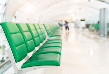 passenger seat in departure hall at airport terminal with sun light, selective focus,transport and travel concept