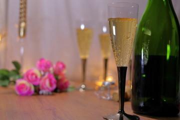テーブルの上にシャンパンとシャンパンボトルと薔薇の花
