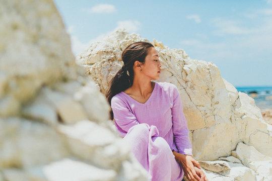 Woman wearing pink dress sitting on rocks