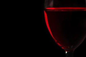 Dark background with a wine glass full of rose wine