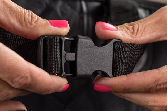 Plastic clasp for a backpack in the hands of a girl with a beautiful manicure