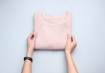 Hands fold knitted sweater on a gray background. Conceptual photo. Top view.