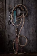 Old scissors and rope hanging on a wooden wall