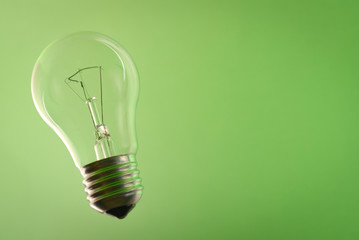 Traditional lightbulb on green background.