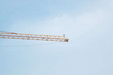 big long yellow  construction crane with Thailand flag and blue sky with white clouds in beautiful day .
