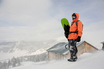 Man standing with the snowboard in hands on the hill near the house