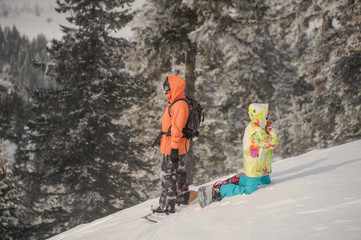 Two snowboarders standing back to back on the hill in the mountain resort
