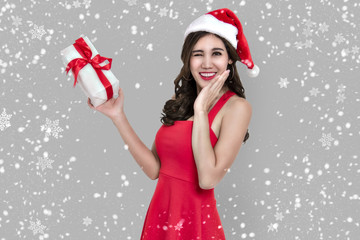 Cheerful young woman in red dress santa holding gift box for christmas isolated on snowflake background.