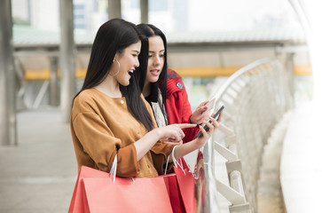 girls holding shopping bags using a smart phone with credit card. cyber monday concept.