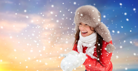 people, season and leisure concept - happy woman in winter fur hat holding snow in her hands outdoors over sky background and snow