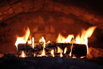 heating of the dwelling during the cold season/ burning oak logs in the roof of the fireplace front view