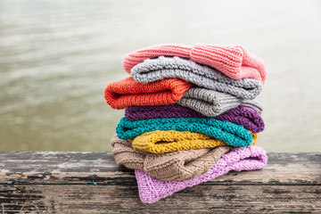 Rows of  colorful knitted hats for sale on  natural background. A colourful collection of bobble hats lined up