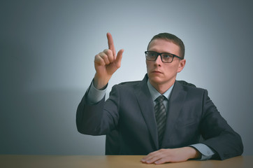 Businessman is pointing by his index finger on a copy space invisible virtual buttons.