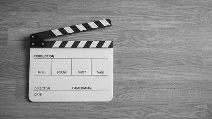 Clapper board or clap board or movie slate use in video production , film, cinema industry. It's white color on wood background.