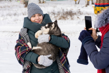 Waist up portrait of modern young woman holding cute Husky puppy and looking at smartphone camera with friend taking photo of her outdoors in winter