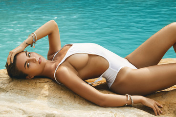 Sexy woman in white swimsuit is posing on the rock