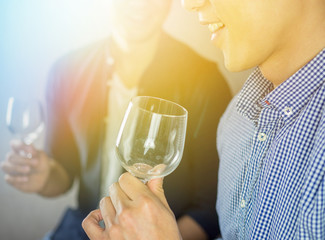 Vintage color effect on men holding glass of wine in the party, close up
