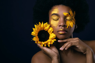 African woman with a sunflower and creative makeup on her face