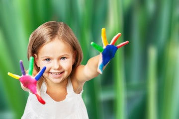 Little girl showing painted hands on bright