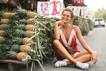 Young and happy woman with a pile of pineapples on the local Thai market