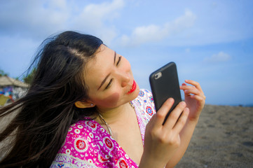 young happy and beautiful Asian Chinese woman taking selfie picture with mobile phone camera at tropical paradise beach during summer holidays travel smiling cheerful