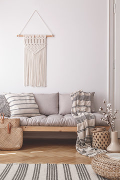 Beige, handmade macrame on a white wall above a couch with a striped linen pillow in a natural living room interior