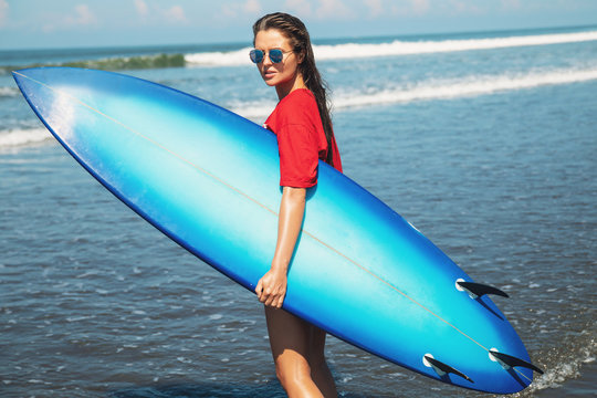 Sexy woman surfer with shortboard on the beach