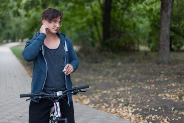 Attractive young caucasian man with dark hair bicycling in the park. Touches the white earphone (airpod). Outdoors, autumn / fall day. Diversity people. Round golden glasses, silver ring. Copy space.