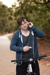 Attractive young caucasian man with dark hair bicycling in the park. Outdoors, autumn / fall park. Diversity people. Melancholy mood. Earphones (airpods), round golden glasses, silver ring.