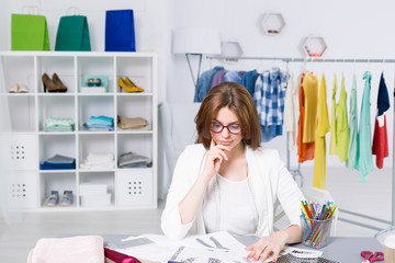 Young woman thinking about her fashion projects in a creative office