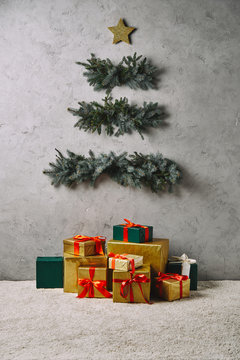 handmade Christmas tree hanging on grey wall, gift boxes on carpet in room