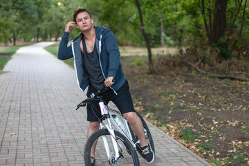 Attractive young caucasian man with dark hair bicycling in the park. Outdoors, early autumn. Diversity people. Melancholy mood. Headphones (earphones, airpods), silver ring, white and rose bicycle.