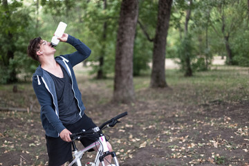 Attractive young caucasian man with dark hair drinks water from sport bin, bicycling in the park. Outdoors, autumn/fall. Headphones (earphones, airpods), golden round glasses, white and rose bicycle.