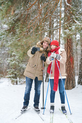 Full length portrait of active young couple taking selfie photo via smartphone while enjoying skiing in snowy winter forest during date