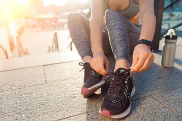 Woman ties shoelaces on sneakers
