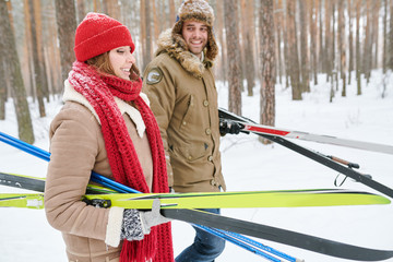 Side view portrait of active young couple carrying skis chatting on the way back in beautiful winter forest, copy space