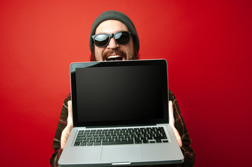 Cheerful smiling young bearded hipster man wearing sunglasses and showing laptop with blank screen, copyspace Wall mural