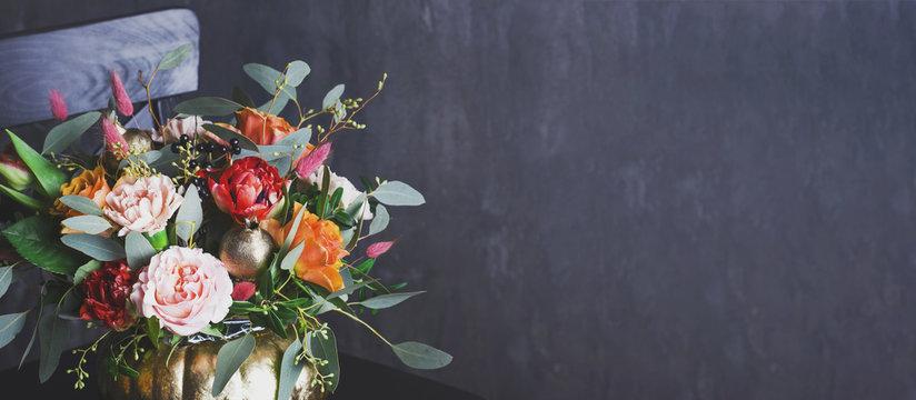 Autumn floral bouquet in punpkin vase on black chair, banner