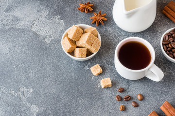 Cup of coffee, brown sugar and cinnamon with anise on concrete background. Copy space