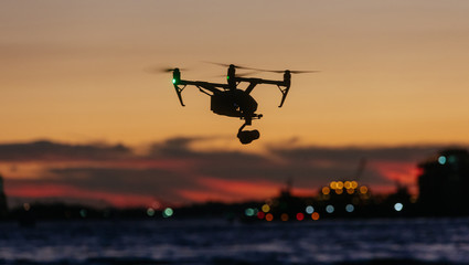 Drone flying and taking pictures of sunset against new york skyline