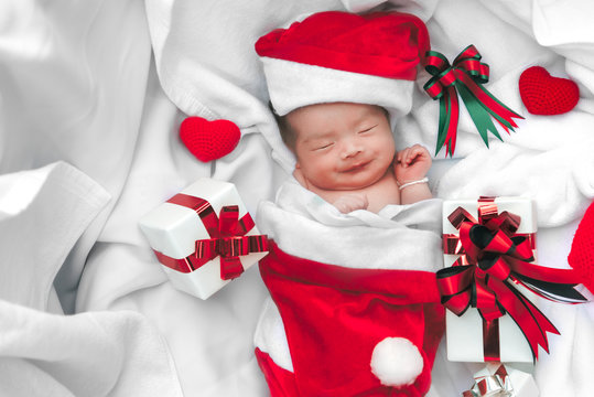 Sleeping newborn baby face in Christmas hat with gift box from Santa Claus and yarn heart on white soft towel. Cute Infant lifestyle and innocent happy baby lying in cold snow season. New year winter