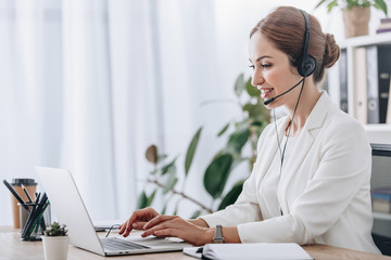 executive female operator working with headset and laptop in call center