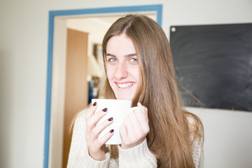 lifestyle morning girl with drink coffee tea in mug at home kitchen room