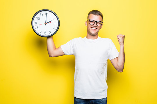 Young handsome man holding alarm clock very happy and excited, winner expression celebrating victory screaming with big smile and raised hands on yellow background